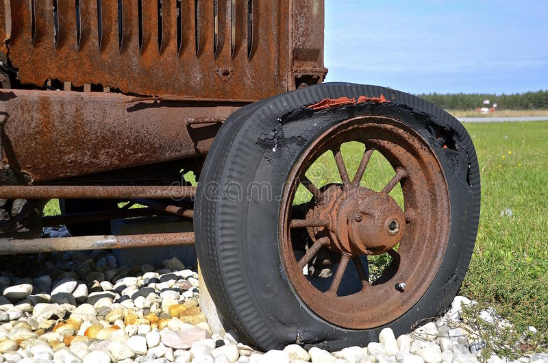 Rotten flat tractor tire. An old rusty tractor is parked on a pile of white rock has a rotten flat front tire stock photos