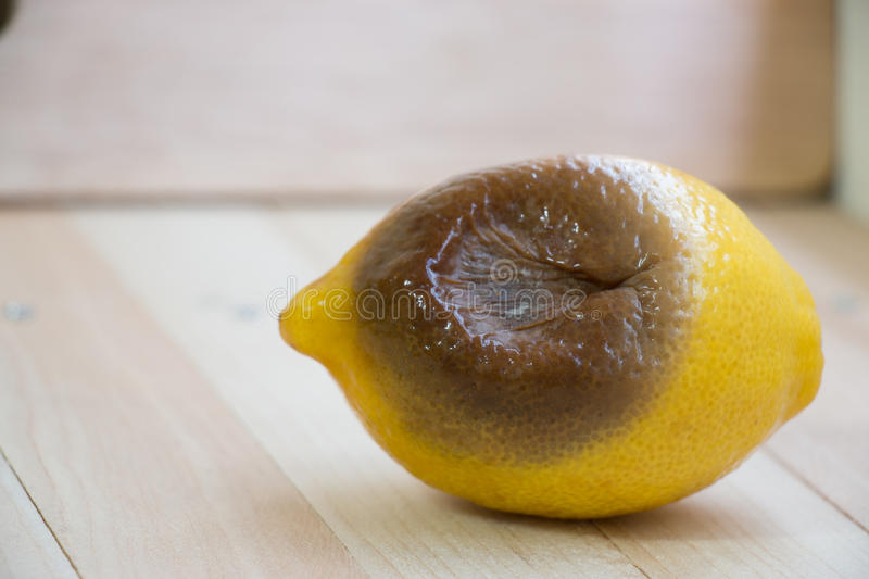 Rotten lemon put on wooden table. Isolate background royalty free stock photo