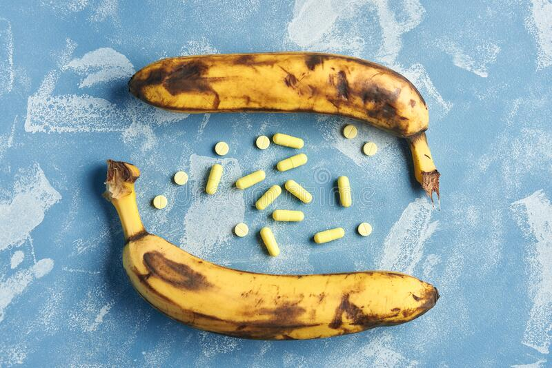 Rotten overripe banana with yellow pills on a blue background. health and pharmacology concept.  royalty free stock photo
