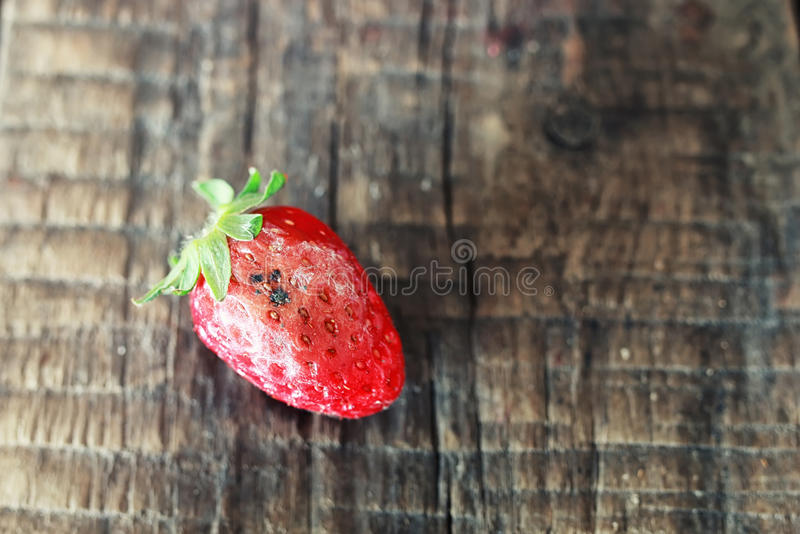 Rotten strawberries on a wooden background. Juicy flavorful red ripe strawberry on a wooden natural background royalty free stock photography