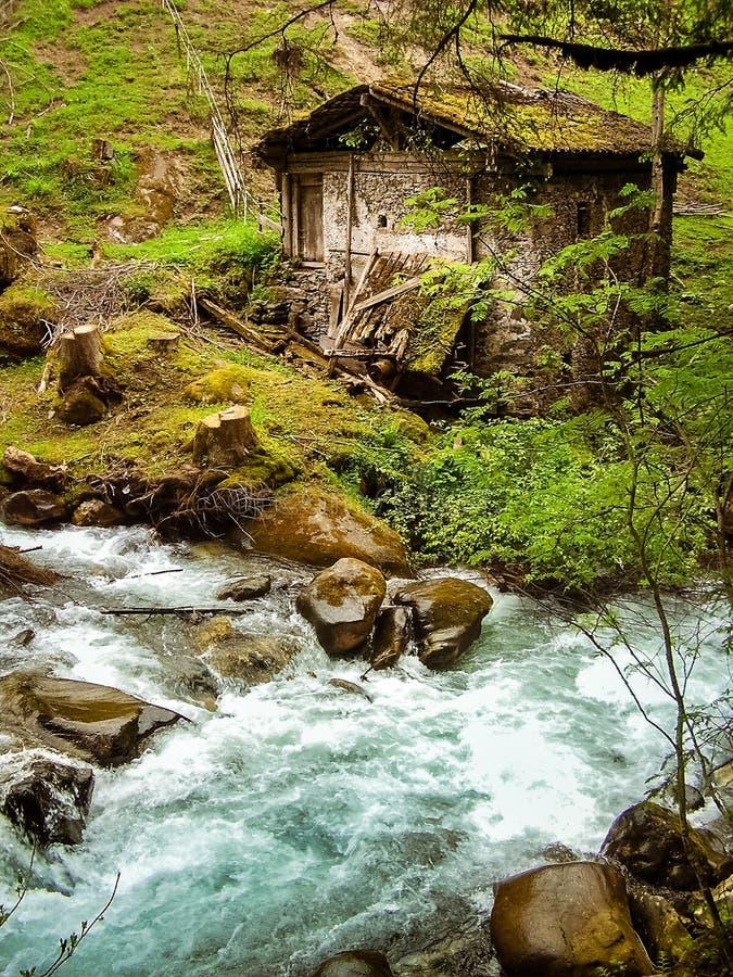 Rottende schuur langs een bergstroom in de Italiaanse Alpen stock foto's