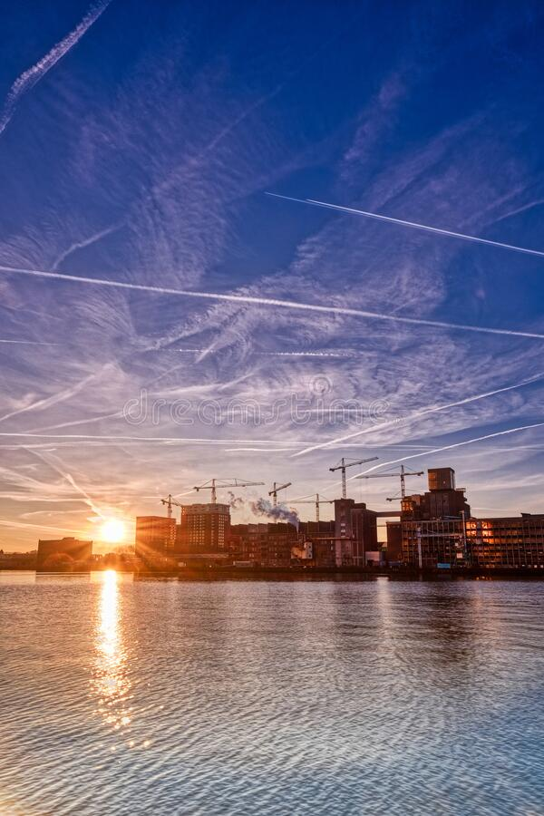 Rotterdam - 14 February 2019: Rotterdam, The Netherlands The sun rises behind several old industrial buildings on the. Waterfront early in the morning, downtown royalty free stock photo
