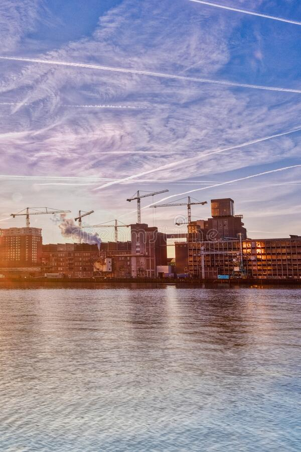 Rotterdam - 14 February 2019: Rotterdam, The Netherlands The sun rises behind several old industrial buildings on the. Waterfront early in the morning, downtown royalty free stock photos