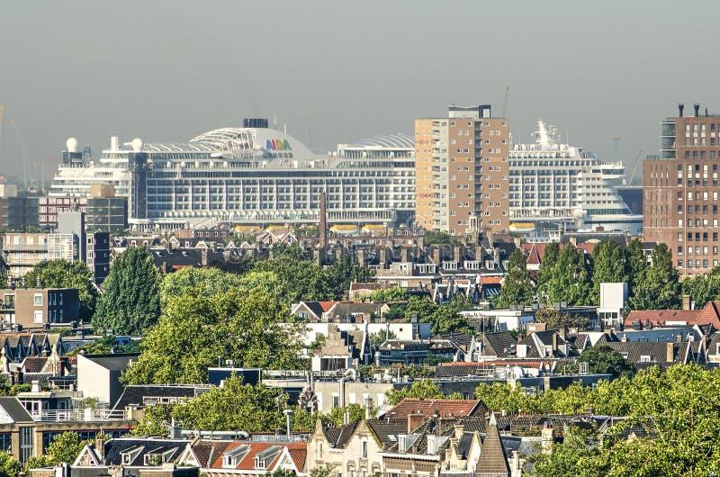 Cruise ship and residential neighbourhoods. Rotterdam, The Netherlands, August 3, 2018: cruiseship Aida Perla is towering over residential neighbourhoods in the stock photo