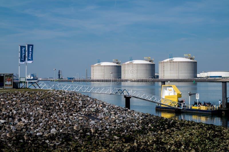 Rotterdam, Paesi Bassi - 19 aprile 2018: Il pilastro del traghetto veloce è vicino ai serbatoi dell'olio nel porto immagine stock libera da diritti