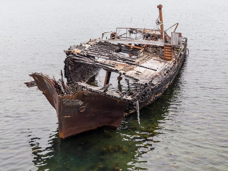 Rotting, abandoned ship on a water of sea, a symbol of decadence and degradation. Barents Sea, Russia royalty free stock image