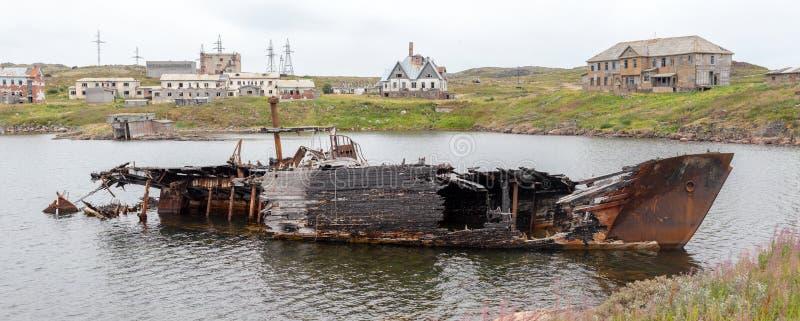 Rotting, navio abandonado em uma água da baía do mar na perspectiva de uma vila abandonada, símbolos da decadência e degradação imagem de stock royalty free