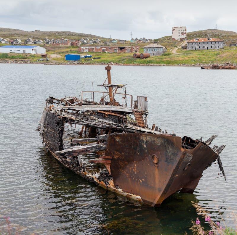 Rotting, navio abandonado em uma água da baía do mar na perspectiva de uma vila abandonada, símbolos da decadência e degradação imagens de stock