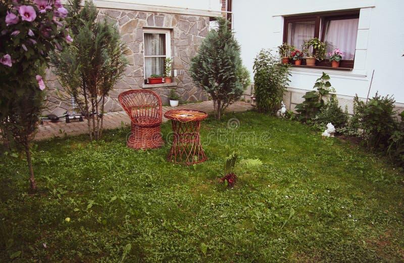 Rottingfåtölj och tabell i en gård och ett grönt gräs arkivbild