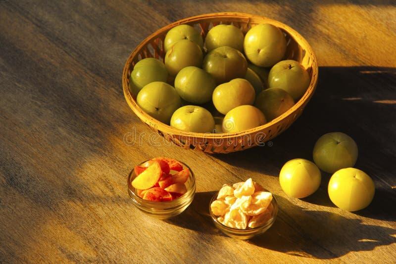 Rottingkorg med krusbäret eller amala med dess biprodukter som isoleras på träbakgrund arkivfoto