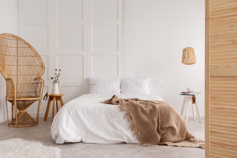 Rottingstol och trätabell bredvid säng med den bruna filten i den vita sovruminre Verkligt foto royaltyfria foton
