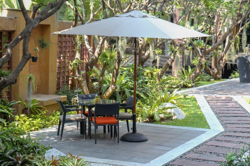 Rottingträdgårdtabell och stolar som äter middag trädgårdstol som är utomhus- i trädgård royaltyfria foton