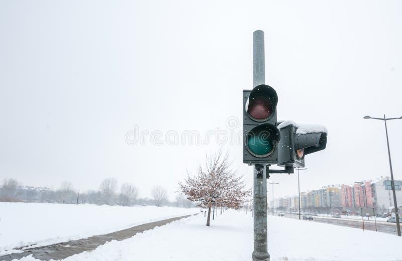 Rotto e dal semaforo di uso sulla passeggiata trasversale della via urbana per i pedoni nella città nociva da neve nell'orario in immagine stock
