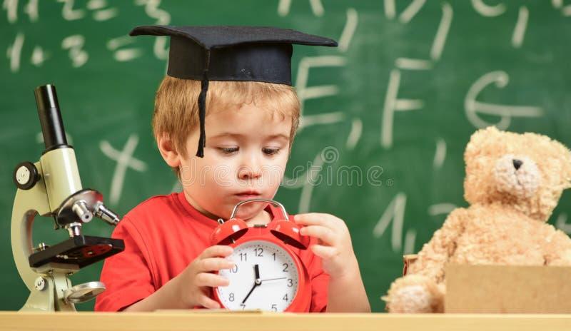 Rottura aspettante della scuola dell'allievo Il bambino sul fronte triste esamina la sveglia Scherzi il ragazzo in cappuccio acca fotografie stock libere da diritti