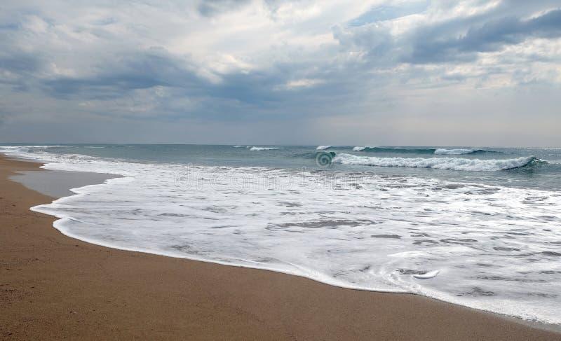 Rotture tempestose delle onde del mare circa la spiaggia vuota sotto il cielo nuvoloso fotografie stock
