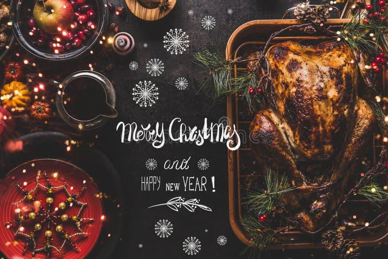 A rotulação de cumprimento do texto do Feliz Natal e do ano novo feliz na tabela de jantar do Natal com o peru roasted inteiro se fotos de stock