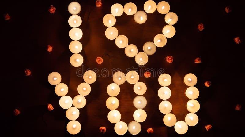A rotulação de incandescência fez EU TE AMO queimando velas Conceito do dia do ` s do Valentim do St foto de stock
