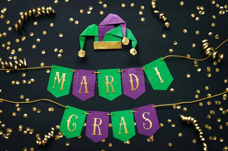 Rotulação dourada de Mardi Gras no verde feito a mão de papel e na festão festiva roxa, fundo preto, confete, chapéu do disfarce  imagem de stock