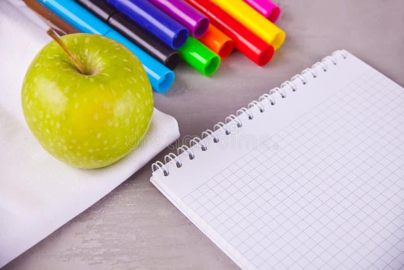 Rotuladores coloridos, cuaderno, manzana verde en el fondo gris Concepto del estudiante o del alumno imagenes de archivo