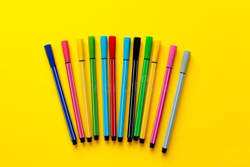 Rotuladores multicolores en fondo amarillo Visión superior, negocio, materiales de oficina Fuentes de direcci?n de la escuela Est foto de archivo