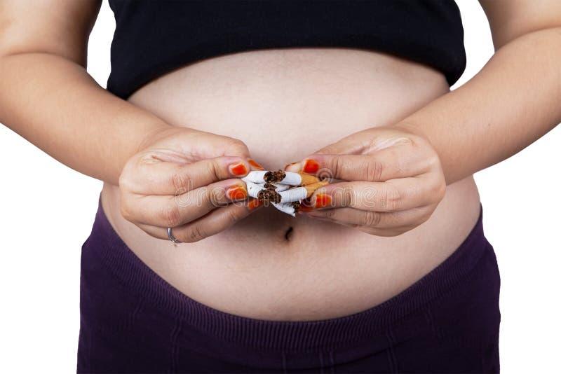 Rotura de la mujer embarazada los cigarrillos fotos de archivo libres de regalías