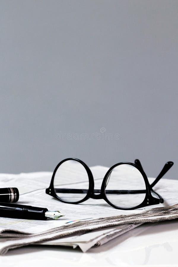 Rotura del periódico con la pluma y los vidrios imagen de archivo