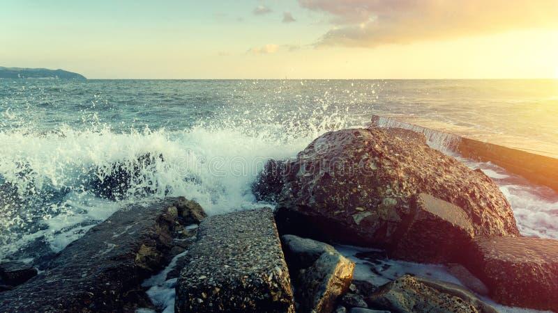 Rotura grande de las ondas en las piedras de Coastal y vuelta en el mar de la espuma en el horizonte y la puesta del sol imágenes de archivo libres de regalías