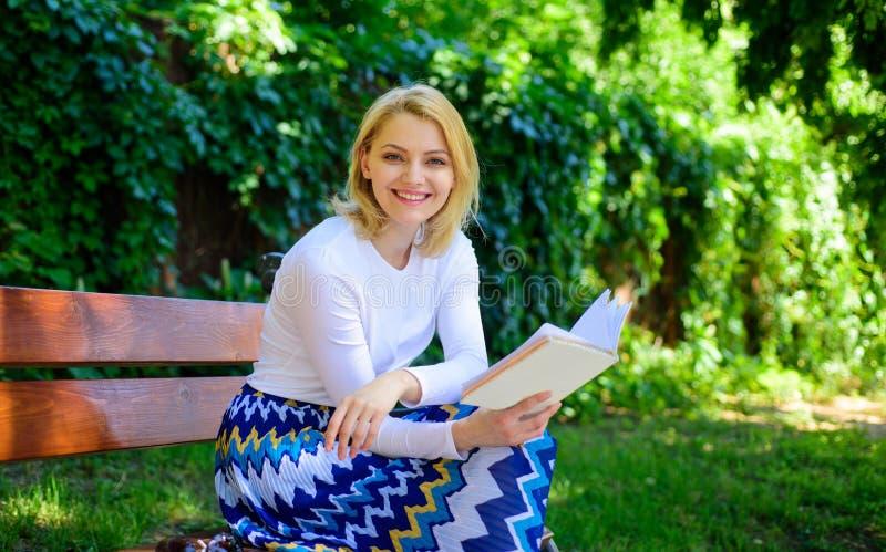Rotura rubia sonriente feliz de la toma de la mujer que se relaja en libro de lectura del jardín La señora disfruta del imrovemen foto de archivo libre de regalías