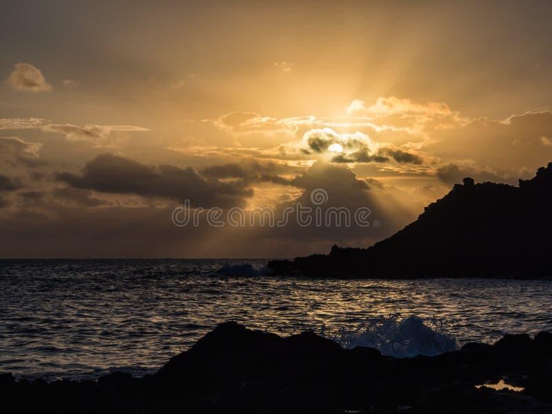 Roturas de la onda de la salida del sol en la roca, Pantelleria, Italia imagenes de archivo
