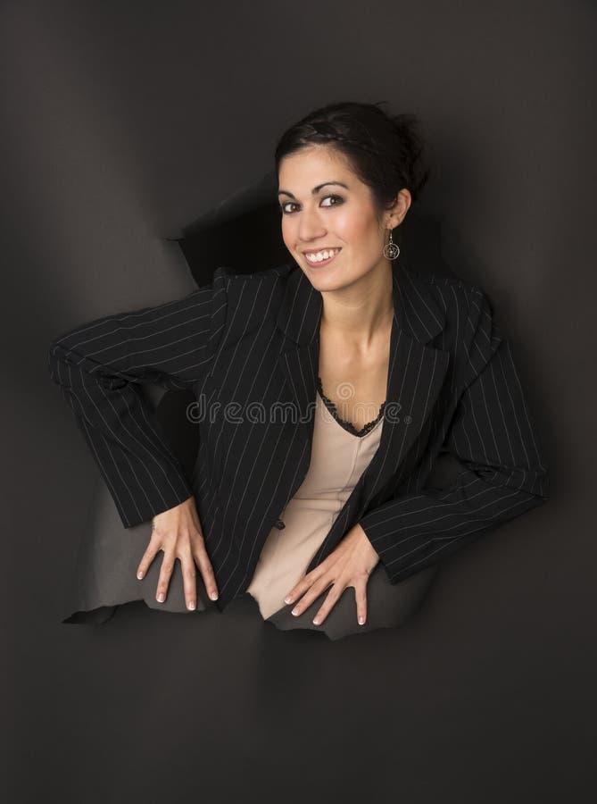 Roturas morenas hermosas de la mujer de negocios a través del agujero de rasgado fotografía de archivo libre de regalías