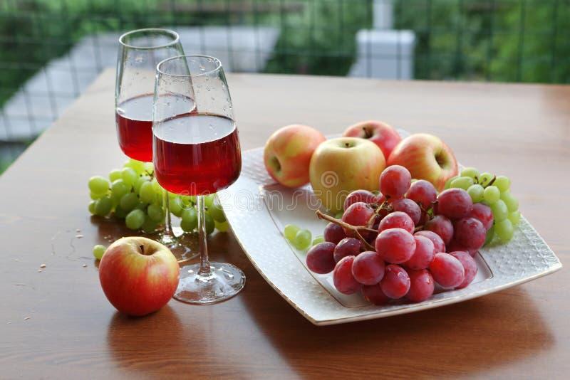 Rotwein in den Gläsern, in den Trauben und in den Äpfeln lizenzfreie stockbilder