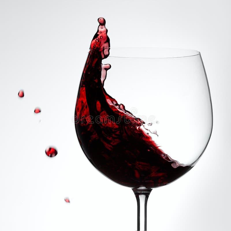 Rotwein, der aus dem trinkenden Glaskonzept heraus spritzt stockfotos