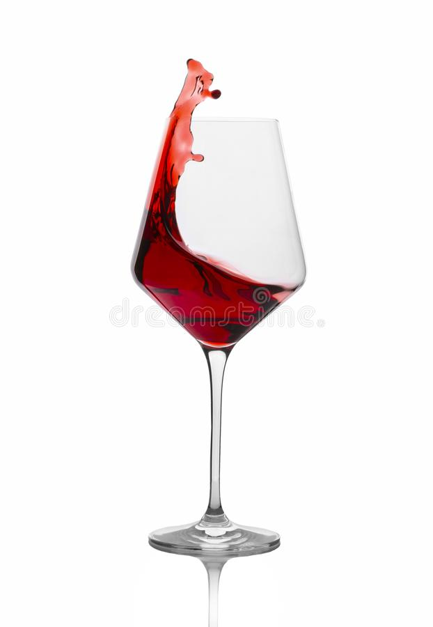 Rotwein, der aus einem Glas heraus lokalisiert auf Weiß spritzt stockfotos