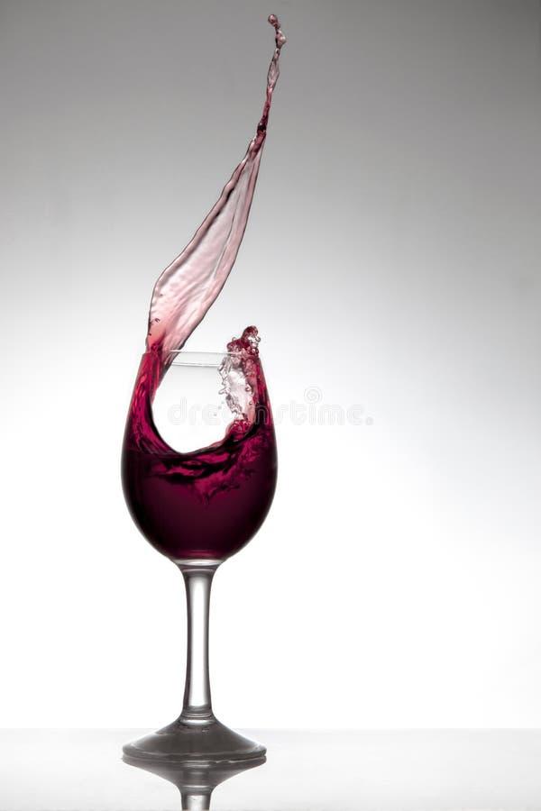 Rotwein, der aus einem Glas heraus spritzt lizenzfreie stockbilder