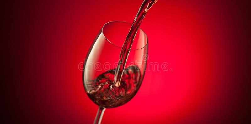 Rotwein, der in ein Glas auf rotem Hintergrund gießt lizenzfreies stockbild