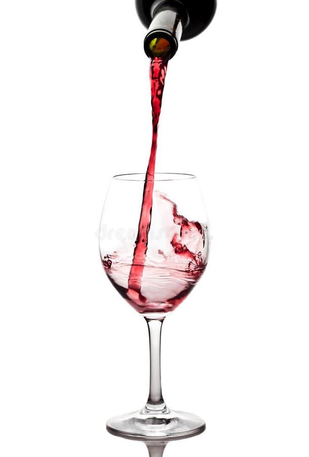 Rotwein, der unten aus einer Weinflasche gießt lizenzfreie stockfotos