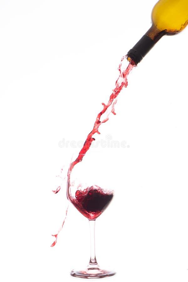 Rotwein, der unten in ein Weinglas gießt lizenzfreie stockfotos