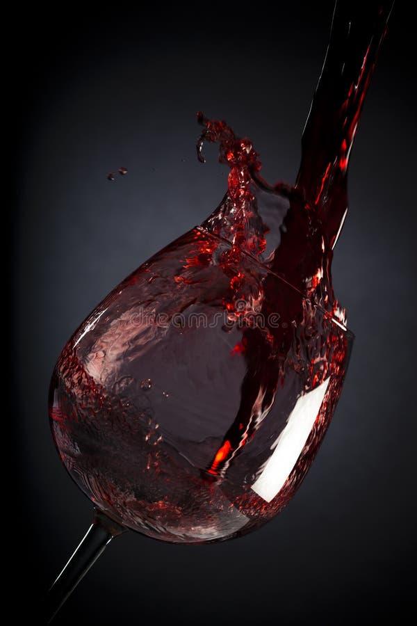 Rotwein, der unten in Weinglas gießt stockfotos