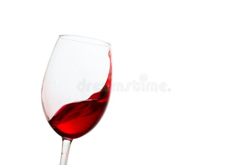 Rotwein, der würdevoll in einem gekippten Glas spritzt stockbild