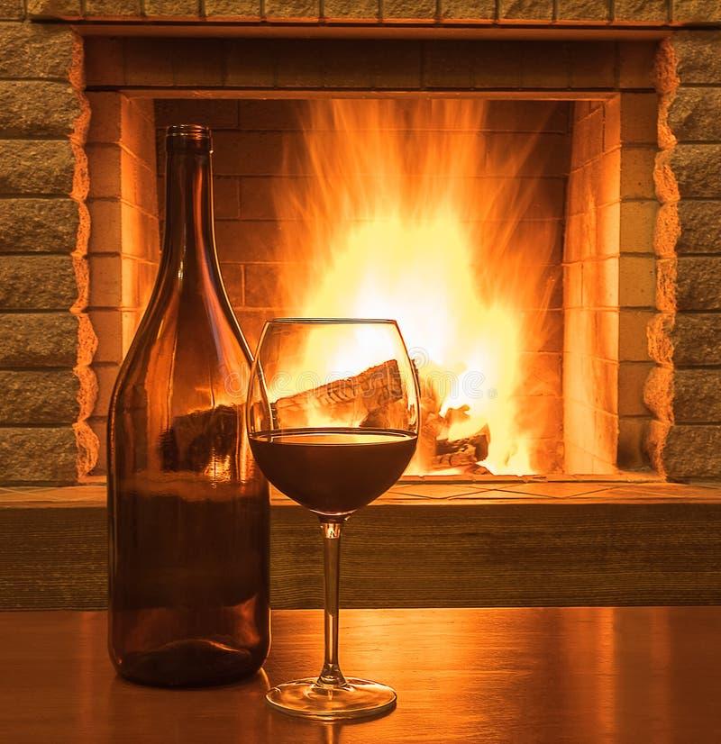 Rotwein in einem Glas und in der Flasche, vor gemütlichem Kamin stockbild