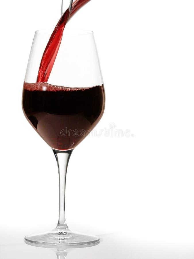 Rotwein gießen herein ein Wein-Glas mit einem Dekantiergefäß stockfotografie