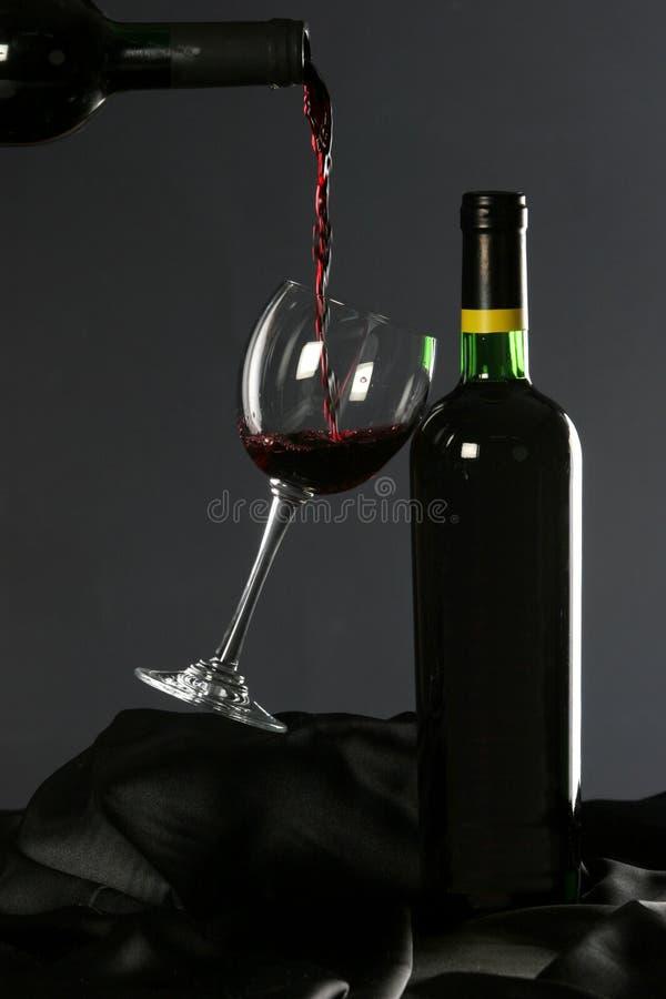Rotwein goss in Weinglas lizenzfreie stockfotografie