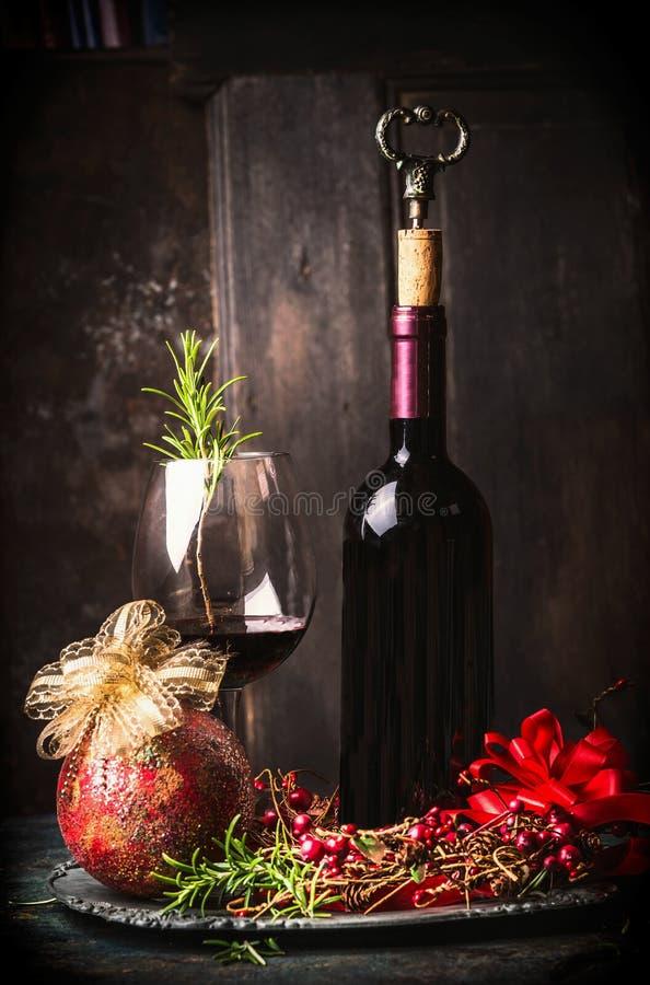 Rotwein im Becher und in der Flasche mit festlicher Weihnachtsdekoration am dunklen hölzernen Hintergrund stockbild