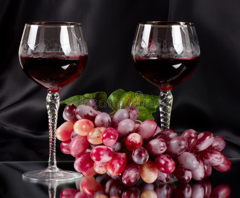 Rotwein im Glas mit Traube lizenzfreies stockfoto