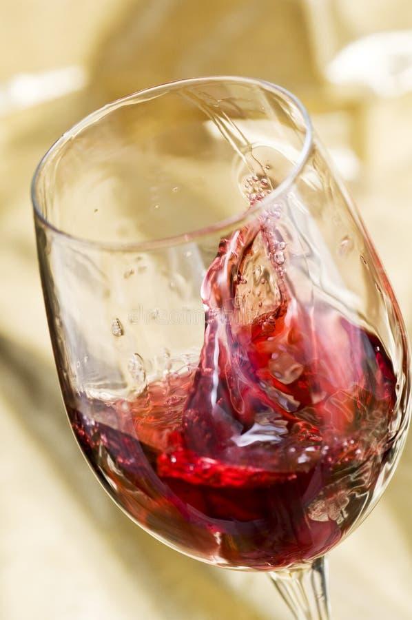 Rotwein spritzt im Glas lizenzfreie stockfotos
