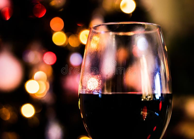 Rotwein vor Weihnachtsbaum mit gelben Lichtern stockbilder