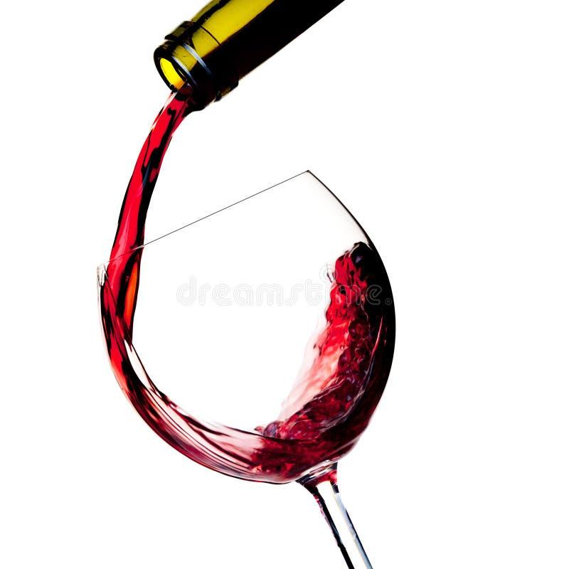 Rotwein wird in ein Glas gegossen lizenzfreie stockfotos