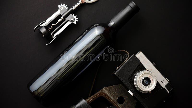 Rotweinflasche, Korkenzieher und alte Fotokamera lizenzfreies stockfoto