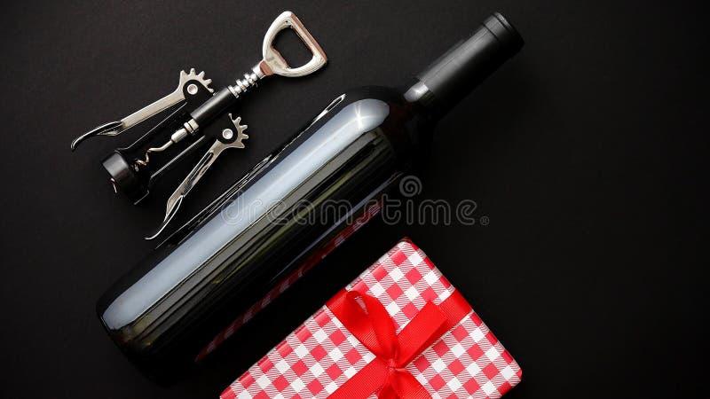 Rotweinflasche, Korkenzieher und eingepacktes Weihnachtsgeschenk lizenzfreie stockfotografie