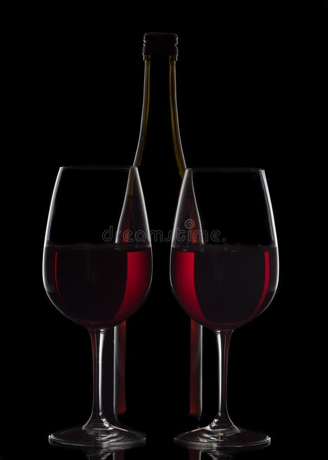 Rotweinflasche und zwei Weingläser auf schwarzem Hintergrund lizenzfreie stockfotos